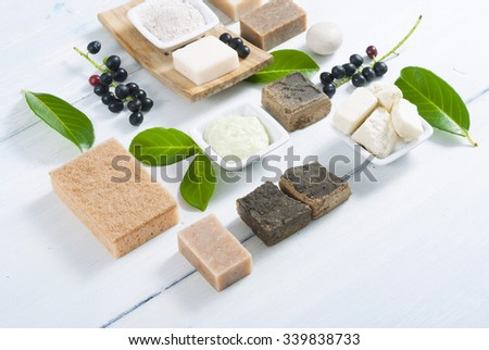 cosmetic clay, soaps, henna blocks, sponge and moisturizer on white wood table