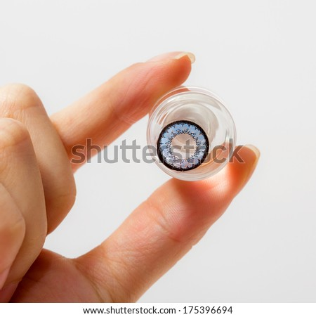 cosmetic contact lenses in bottle with  hand