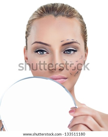 Cosmetic correction surgery, woman before plastic surgery looking in mirror - stock photo