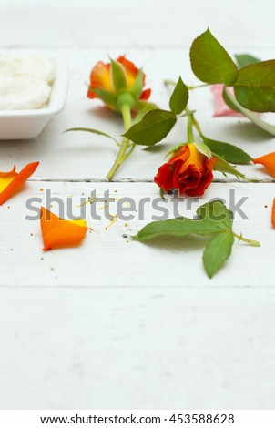 cosmetic cream and rose flowers, petals on white wooden table background