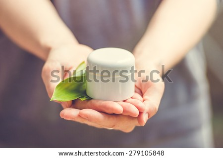 Cosmetic cream container with green herbal leaves in woman hands. Toned image - stock photo