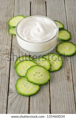 cosmetic cream in glass jar with cucumber slices, wood table - stock photo