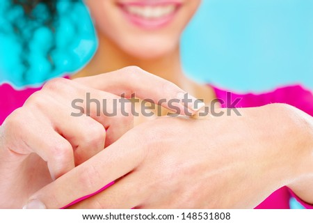 cosmetic cream on hand and girl's big smile behind