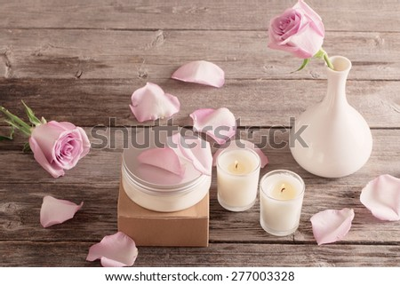 cosmetic cream with pink roses and candle  on old wooden table - stock photo