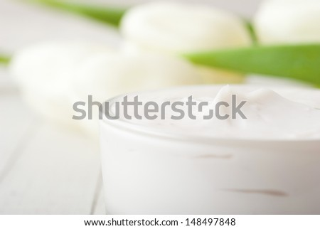 cosmetic cream with tulips on white wooden  - stock photo