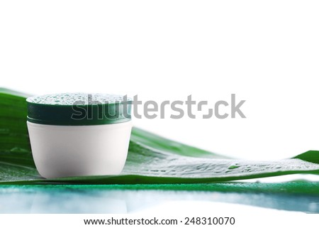 Cosmetic cream with water drops on green leaves on light background - stock photo