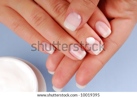 Cosmetic. Drop of moisturizer on the middle woman finger.