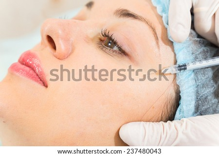 Cosmetic injection in the spa salon. Beautician makes injection into the patient's face. the concept of rejuvenation.