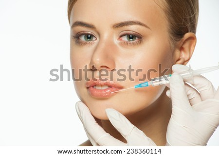 Cosmetic injection of botox to the pretty female lips. Healthcare and beauty concept - stock photo
