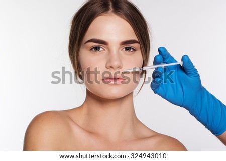Cosmetic injection of hyaluronic acid to the young woman's lips. Isolated on white background - stock photo
