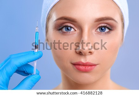 Cosmetic injection on the pretty woman face. Isolated on blue background - stock photo