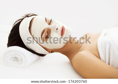 Cosmetic Mask. Beautiful Young Woman Getting a Beauty Treatment in Spa Salon. Isolated on White Backround - stock photo
