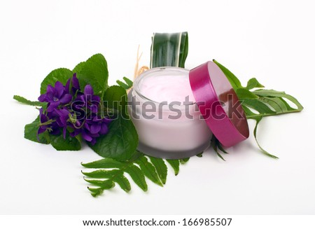 Cosmetic pink cream with herbs and flowers on white background