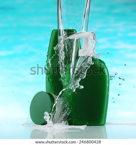 Cosmetic products in water splashes on blue background - stock photo