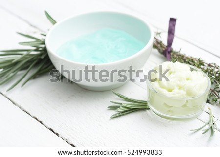 cosmetic products with lavender and thyme leaves on white wooden table background