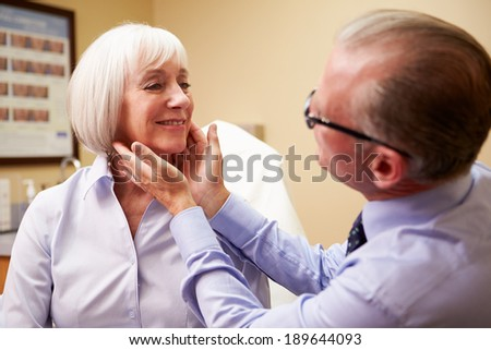 Cosmetic Surgeon Examining Senior Female Client In Office