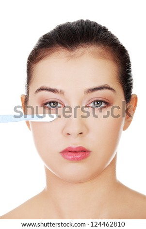 Cosmetic surgery concept. Female face in background of scalpel. - stock photo