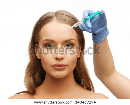cosmetic surgery concept - woman face and beautician hand with syringe - stock photo