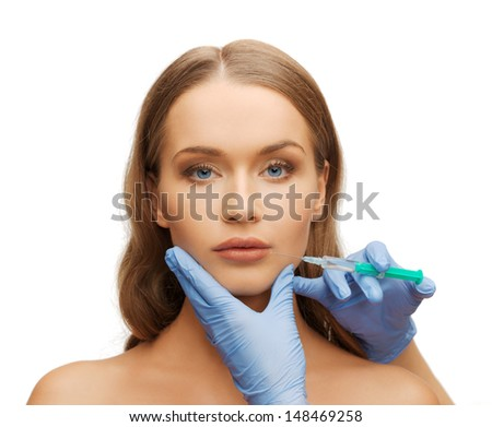 cosmetic surgery concept - woman face and beautician hands with syringe - stock photo