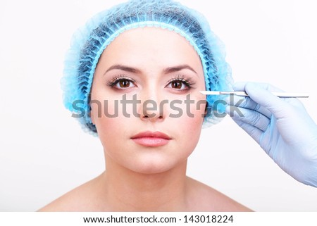 Cosmetic surgery with scalpel on young woman close up - stock photo