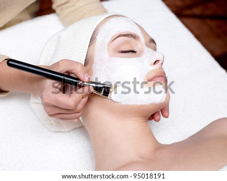 Cosmetician applying facial beauty mask for young beautiful woman at spa salon