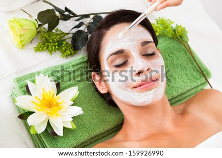 Cosmetician Applying Facial Beauty Mask For Young Woman At Spa Salon - stock photo