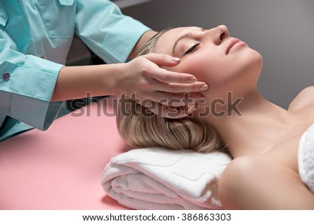 Cosmetician doing the massage. the beautician does a head massage the client . Blonde girl lies on a couch and relaxes.