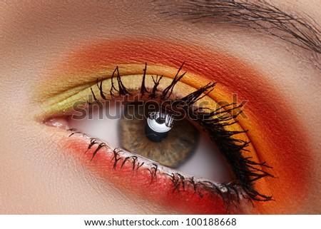 Cosmetics and beauty care. Macro close-up of beautiful green female eye with bright fashion runway make-up. Rainbow eyeshadows and black eyeliner - stock photo