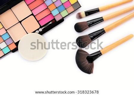 Cosmetics and brushes on white background. - stock photo