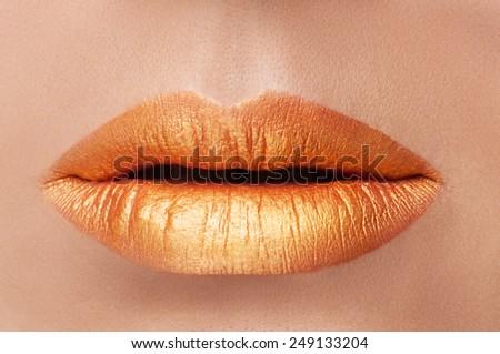 Cosmetics and make-up. Close-up shoot of a beautiful woman with golden lips lipstick and gloss. Golden creative lip gloss. Sweet kiss. Close-up of beautiful full lips girl. Beautiful skin. - stock photo