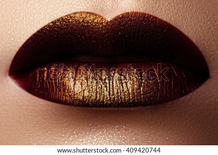 Cosmetics and make-up. Shoot of a beautiful girl with golden lips lipstick and gloss. Sexy and stylish lips. Lips against the backdrop of smooth skin - stock photo