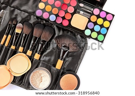 Cosmetics and makeup tools on white background.