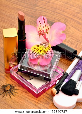 Cosmetics and orchid on wooden background, closeup