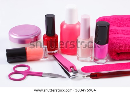 Cosmetics and set of manicure or pedicure tools, nail file, nail polish and remover, scissors, nail clippers, fluffy towel, concept of nail care - stock photo