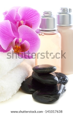 Cosmetics and towels with pink orchid on a white background.