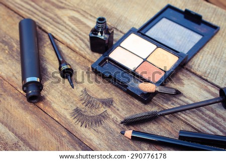 Cosmetics for eyes: pencil, mascara, eyeliner, false eyelashes and eye shadow. Toned image.  - stock photo