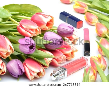 Cosmetics for women's makeup lipstick, lip gloss and tulip flowers on a white background - stock photo