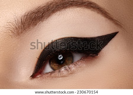 Cosmetics & make-up. Beautiful female eye with sexy black liner makeup. Fashion big arrow shape on woman's eyelid. Chic evening make-up  - stock photo