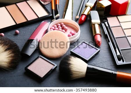 Cosmetics on dark background, closeup - stock photo