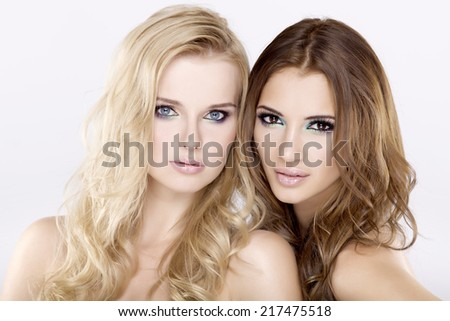 Cosmetics portrait of two smiling young adult attractive and sensuality girl friends - blonde and brunette on white background - stock photo