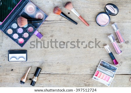 Cosmetics with eye shadow, eye liner and powder on wood table with copy space. Top view. - stock photo