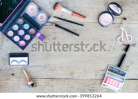 Cosmetics with eye shadow, eye liner, powder, eyelash curler on wood table. Top view. - stock photo