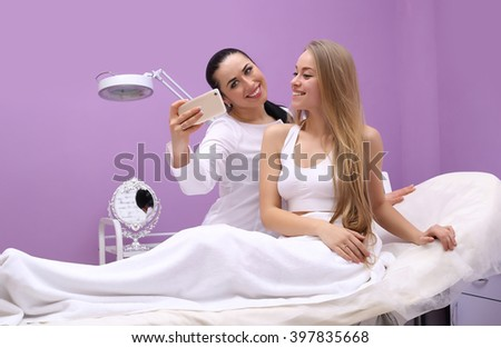 Cosmetology. After the procedure, lip augmentation, beauticians and patient do share photos, selfie phone. - stock photo