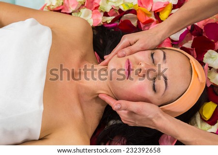 Cosmetology spa facial. Beautiful brunette in a spa salon. Girl lying on petals of roses in a beauty salon.?osmetology, beautician, beautiful background - concept of a facial care.