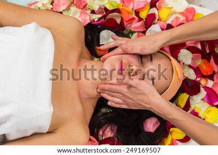 Cosmetology spa facial. Beautiful brunette in a spa salon. Girl lying on petals of roses in a beauty salon.Cosmetology, beautician, beautiful background - concept of a facial care.