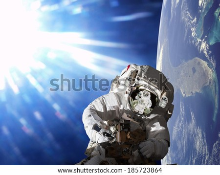 cosmonaut working in space on earth background. Elements of this image furnished by NASA.  - stock photo