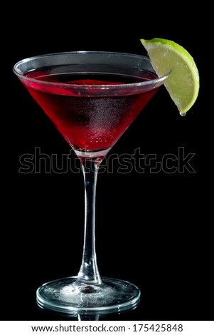 cosmopolitan martini served with a lime isolated on a black background - stock photo