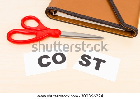 Cost in paper cut by scissor on wooden desk concept cost cut