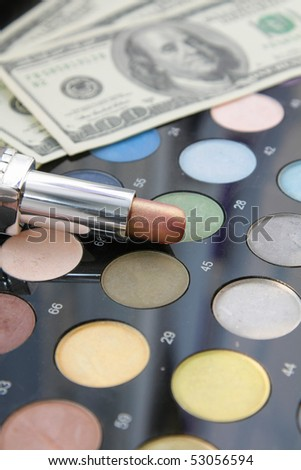 Cost of beauty. On a palette of powder brush and eye shadows there is lipstick in focus, on a background dollars