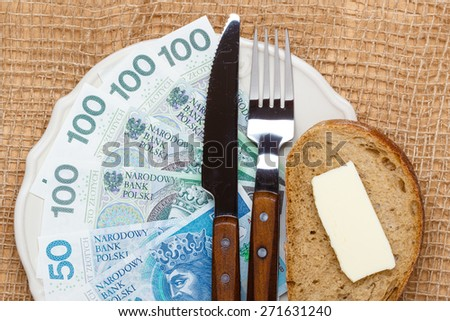 Cost of living, price of eating food budget concept. Polish money on kitchen table, piece of bread on plate